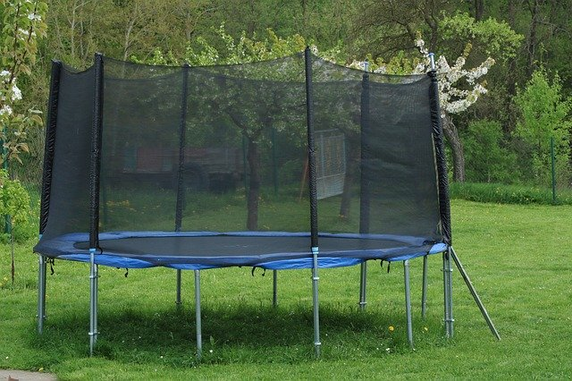 modročerná trampolína na zahradě